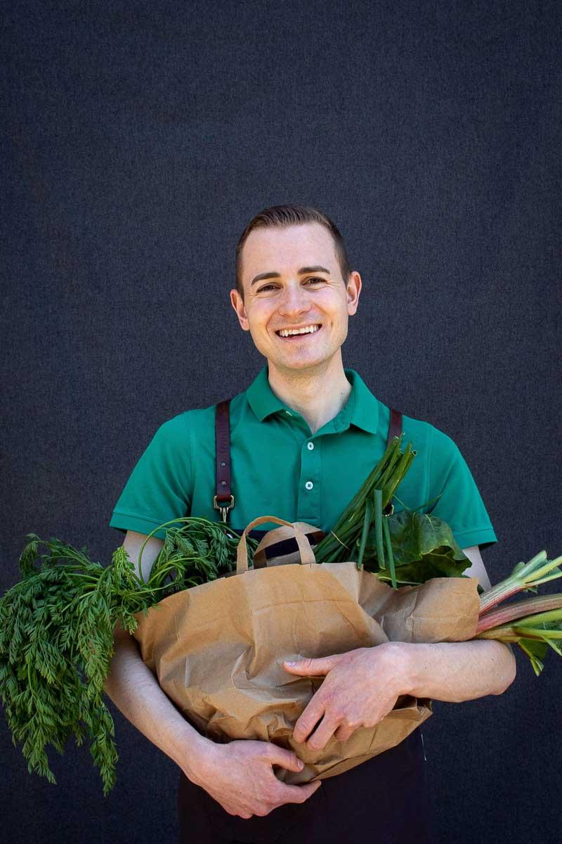 Portrait Frederik Schafmeister mit Gemüse-Einkäufen vom Markt